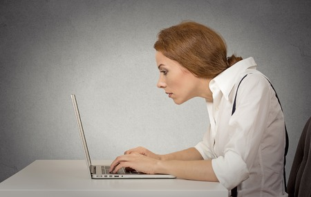 Young woman working on computer sitting at desk isolated on grey wall gloomy office background with copy space. Long monotonous tiresome working hours life concept