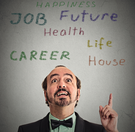 reconsider: Closeup headshot happy middle aged business man looking pointing up with finger at many life choices isolated grey wall background with text. Human face expression perception vision priorities concept Stock Photo