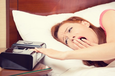deprivation: Closeup portrait woman extending hand to alarm clock yawning lies in bed trying to wake up for new day. Human face expression, emotion, feeling. Sleep deprivation, lack of adequate sleep concept