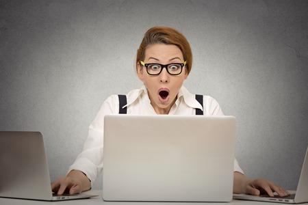 medios de comunicaci�n social: Esto es demasiado! Joven no puede manejar la carga de trabajo m�s. Multitarea ocupado tratando de manejar todo por s� misma trabajando en varios ordenadores al mismo tiempo sentado en el escritorio en la oficina. Expresi�n de la cara