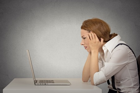 Portrait stressed young unhappy business woman working on laptop siting at desk isolated grey wall office background. Long working hours, complicated software concept. Negative face expression emotion Banque d'images