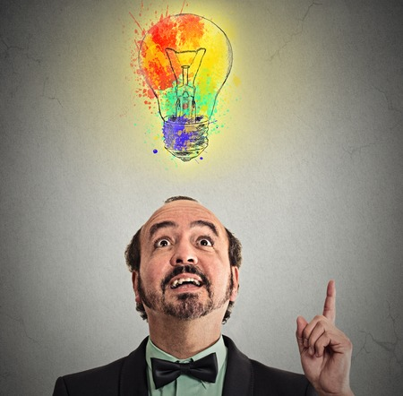 business for the middle: Concept of Creative business idea with colorful lightbulb. Middle aged business man came up with solution answer for a problem looking pointing with finger up isolated on grey wall background
