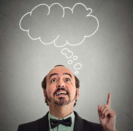 bubbly: Portrait middle aged man has idea happy excited pointing with finger up looking up, speech bubble banner above head isolated grey wall background. Businessman with solution. Face expression perception Stock Photo