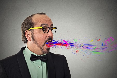 linguist: Side profile view portrait headshot man talking singing open mouth colorful splash abstract notes waves flying away isolated grey wall background. Human face expression emotion. Communication concept