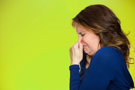 adverse reaction: Closeup side profile portrait unhappy middle age woman covers pinches  her nose something stinks very bad smell situation, isolated green background with copy space. Human facial expression emotion