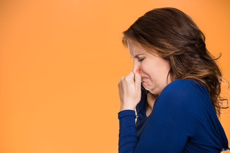 adverse reaction: Closeup side profile portrait unhappy middle age woman covers pinches  her nose something stinks very bad smell situation, isolated orange background with copy space. Human facial expression emotion