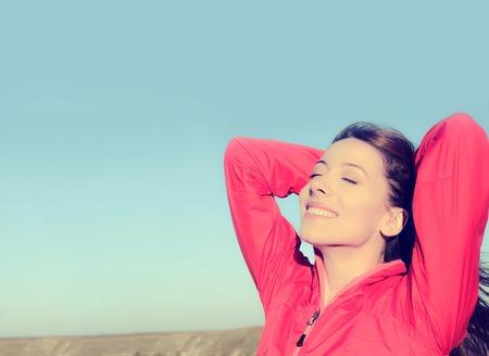 Vrouw lachend armen omhoog naar de blauwe hemel, het vieren van de vrijheid. Positieve menselijke emoties, gezichtsuitdrukking gevoel leven perceptie succes, gemoedsrust concept. Gratis Gelukkig meisje op het strand genieten van de natuur