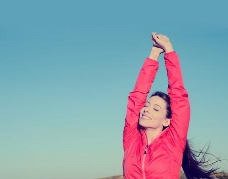 Donna sorridente braccia sollevate al cielo blu, che celebra la libertà. Emozioni umane positive, espressione faccia sentimento successo percezione vita, la pace della mente concetto. Ragazza felice libero sulla spiaggia godersi la natura