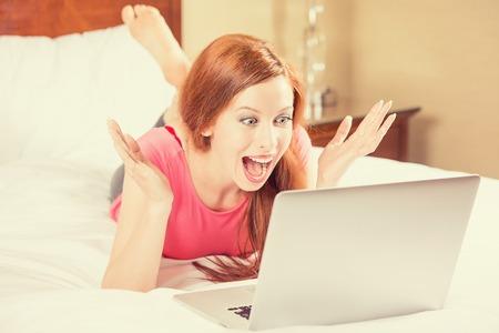 wow: Hermosa mujer joven emocionada con los brazos levantados con mirar a la pantalla de su computadora port�til que pone en la cama. Expresi�n positiva emoci�n humana feliz facial, el lenguaje corporal, la reacci�n. Inesperado agradable buena noticia