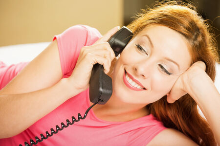 answering call: Portrait beautiful young happy woman talking on a phone lying in bed making hotel room service oder. Positive human face expression emotion feeling. Communication, leisure, travel concept