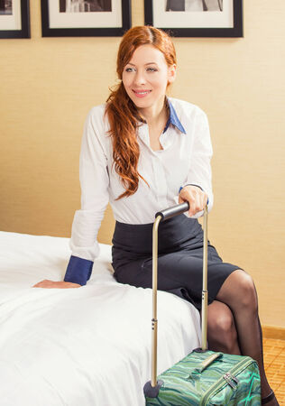girl sit: Smiling happy young business woman sitting on bed in hotel room ready for next trip. Positive face expression. Business trip traveler concept. Corporate employee entrepreneur working lifestyle