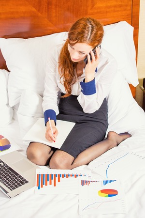 topicality: Business woman talking on mobile phone working on laptop in hotel room top view. Corporate executive, traveler life style on a move concept. Stock Photo
