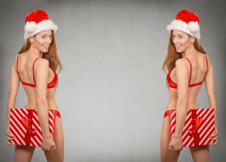 Portrait beautiful young sexy christmas woman in santa hat wearing red lingerie holding gift box isolated grey wall background copy space. Holiday season concept. Positive face expression, emotion