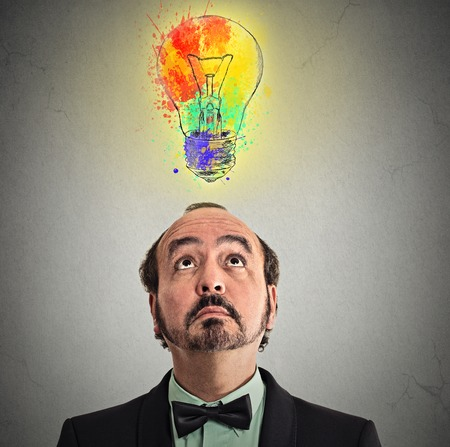 business for the middle: Concept of Creative business idea with colorful lightbulb. Portrait middle aged businessman came up with solution answer for problem looking up isolated on grey wall background. Perception vision