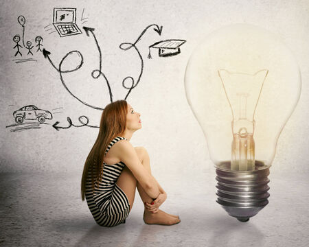 brain power: Young woman sitting in front of light bulb thinking has many thoughts life ideas isolated on grey wall background. Human face expression motivation perception vision, brain power, imagination concept Stock Photo