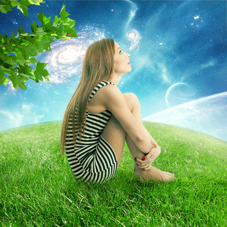 stargazing: Thoughtful young woman sitting on on a green meadow earth planet looking up at starry sky with moonlight. Ecology eco friendly world concept. Dreamland outdoors relaxation environment  screen saver Stock Photo