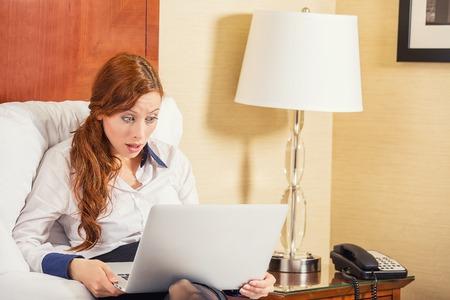 stupor: Sorprendido mujer de negocios joven usando la computadora port�til mirando la pantalla del ordenador vuelen por los estupor sentado en la cama en su casa, hotel. La expresi�n humana cara, emoci�n, sensaci�n, percepci�n, lenguaje corporal, la reacci�n