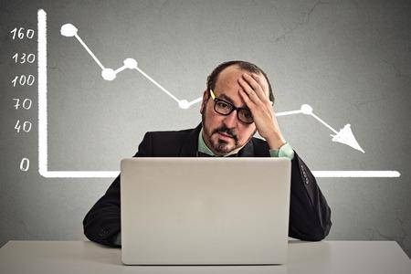 dolor de cabeza: Frustrado hombre de negocios tensionado que se sienta a la mesa en frente de la computadora con el gr�fico de la carta del mercado financiero que va abajo en el fondo gris de la pared de la oficina. Pobre concepto de la econom�a. Expresi�n de la cara, emoci�n