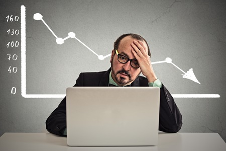 going down: Frustrated stressed business man sitting at table in front of computer with financial market chart graphic going down on grey office wall background. Poor economy concept. Face expression, emotion