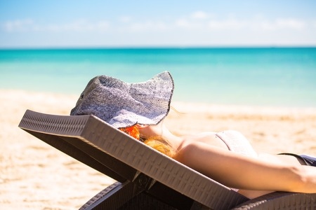 Young woman with sun hat enjoying the sea view sitting laying on a beachs chair close to the sea blue ocean. Travel tropical vacation paradise nature getaway freedom concept