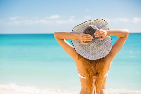 Happy young woman enjoying beach relaxing joyful in summer by tropical blue water. Beautiful bikini model happy on travel wearing beach sun hat on. Beach fun vacation, travel concept