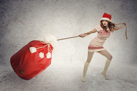 Young santa helper girl pulling heavy christmas sack isolated on grey wall background. Holiday shopping concept photo