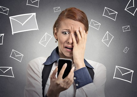 disgusted: Upset stressed woman holding cellphone disgusted shocked with message she received isolated grey background. Funny looking human face expression emotion feeling reaction life perception body language Stock Photo