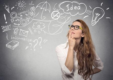soñar carro: Retrato de joven feliz soñando mujer de pensamiento tiene muchas ideas mirando hacia arriba aislados fondo gris de la pared. Positivo expresión de la cara percepción sentimiento emoción la vida humana. Toma de decisiones concepto proceso.
