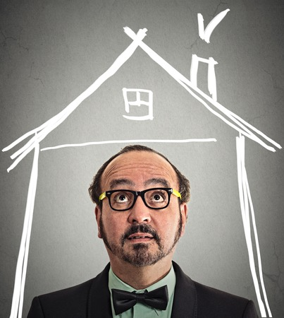 financial questions: closeup portrait headshot businessman looking up house roof above head isolated grey wall background with copyspace. Human face expression life perception. Security safety concept. Real estate market Stock Photo