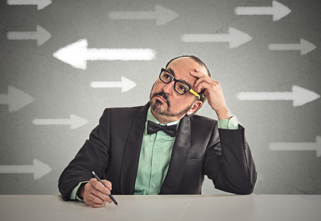 hesitation: Uncertain guy looking at arrows. Man full of doubts hesitation. Closeup portrait puzzled business man thinking deciding something confused unsure isolated grey wall background. Emotion face expression Stock Photo