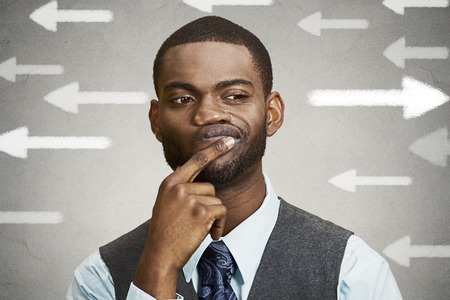 face expression: Uncertain guy looking at arrows. Man full of doubts hesitation. Closeup portrait puzzled business man thinking deciding something confused unsure isolated grey wall background. Emotion face expression Stock Photo