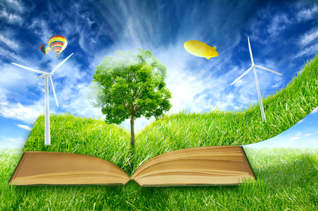 image of green micro world, book covered with green grass wind energy with turbines installed. Sustainable source of electricity, power supply concept. Eco environmentally friendly technology approach photo