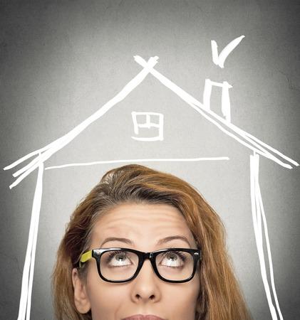 コピー スペースと灰色の壁の背景で隔離の頭の上の家の屋根を探しているクローズ アップの肖像画のヘッド女性。人間の顔の表現の生活の知覚。セ