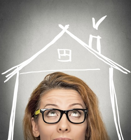 roof top: closeup portrait headshot woman looking up house roof above head isolated on grey wall background with copy space. Human face expression life perception. Security safety concept. Real estate market Stock Photo