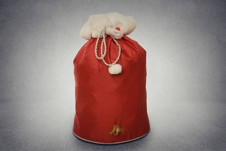 sackful: Santa Claus red bag full with gifts isolated on grey wall texture background with copy space. Holiday season concept. Shopper sale deals