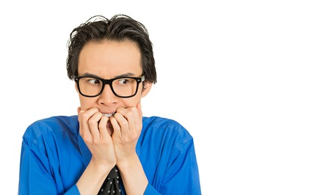 crave: Closeup portrait nerdy young guy with black glasses biting his nails craving something looking anxious isolated white background. Human face expression emotion feeling perception body language Stock Photo