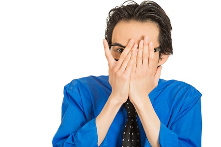 snooping: Closeup portrait young shy timid man covering face with hands with space to peek through isolated white background. Human emotion facial expression feelings, reaction life perception body language Stock Photo