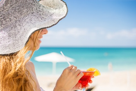 caribbean drink: Young woman in white swimsuit with cocktail on the beach enjoying sunny weather looking on the ocean view. Tropical paradise getaway travel vacation tourism concept. Positive emotion face expression Stock Photo