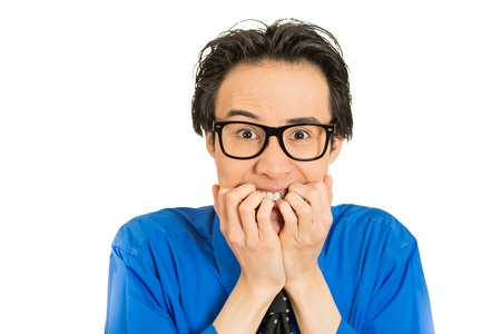 self conscious: Closeup portrait nerdy young guy with black glasses biting his nails craving something looking anxious isolated white background. Human face expression emotion feeling perception body language Stock Photo
