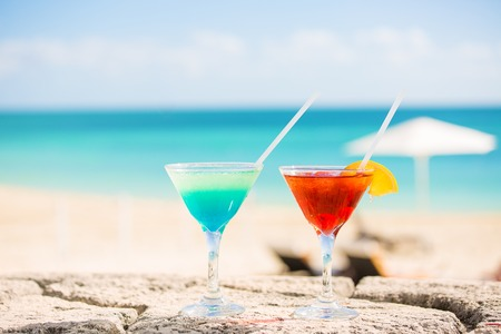 Two tropical cocktails on tropical beach ocean white sand and seascape. Travel, leisure, holiday, paradise getaway, vacation escape, tourism concept photo