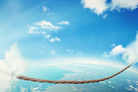 balancing act: Managing risk big business challenges uncertainty concept. Walking on dangerous rope high in sky symbol of balance overcoming fear for goal success. Young entrepreneur in corporate world balancing act Stock Photo