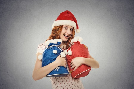 errands: Young happy santa helper in red hat holding gift sacks isolated on grey wall background with copy space. Positive face expression. Santa claus is coming. Holiday season concept