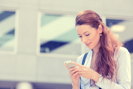business woman phone: Closeup portrait, happy, cheerful, girl, excited by what she sees on cell phone, isolated background corporate office. Facial expression, reaction. Business woman sending text message from her mobile
