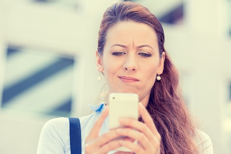 conflictos sociales: Perfil lateral del primer retrato trastorno triste escéptico mujer seria infeliz hablar enviando mensajes de texto en el teléfono disgustado con la conversación aislada ciudad de fondo. Emoción humana sentimiento expresión de la cara negativa Foto de archivo