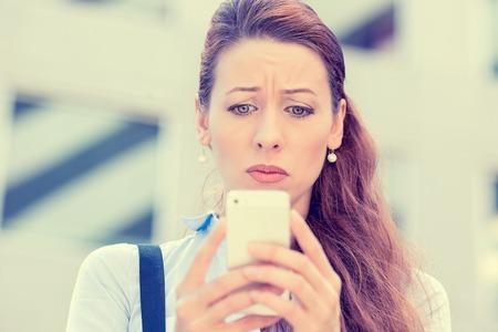 Malestar destacó la mujer sosteniendo teléfono celular disgustado con el mensaje que recibió el fondo aislado edificio corporativo. Triste que mira cara emoción expresión humana sentirse reacción lenguaje corporal percepción
