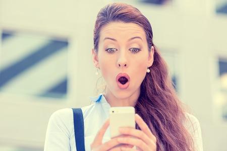 Close-up portret angstig jong meisje op zoek naar de telefoon zien van slecht nieuws of foto's met walgelijke emotie op haar gezicht geïsoleerd buiten de stad achtergrond. Menselijke emotie, reactie, expressie