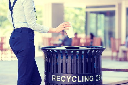 recycle: Closeup cropped image womans hand throwing empty paper coffee cup in recycling bin, isolated outside, trees background. Recycling, eco friendly approach concept. Keep streets, city, earth clean