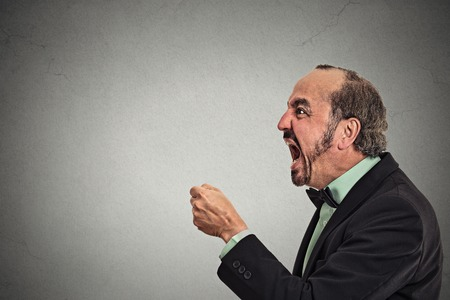 angry teacher: Side profile portrait bitter mad displeased pissed off angry grumpy corporate man open mouth fist in air, screaming, yelling isolated grey background. Negative human emotion facial expression feeling Stock Photo