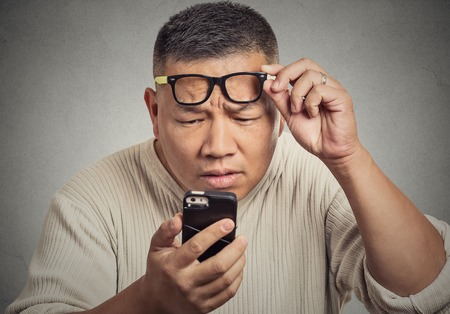 Closeup portrait headshot middle aged man with glasses having trouble seeing cell phone screen because of vision problems. Bad text message. Negative human emotion facial expression feeling perception