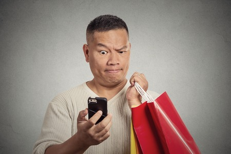asian shopper: Portrait surprised funny man holding red shopping bags looking at smart phone shocked discovered great online deal. Human emotion facial expression body language reaction. Holiday season sale concept